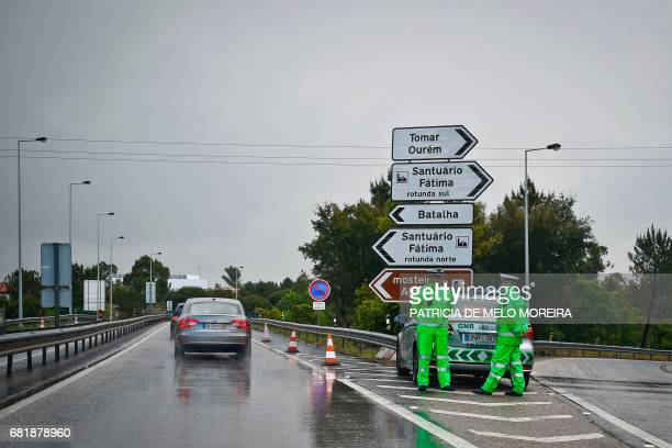 Traffic police stand on the highway exit to Fatima shrine central Portugal on May 11 2017 Two of the three child shepherds who reported apparitions...