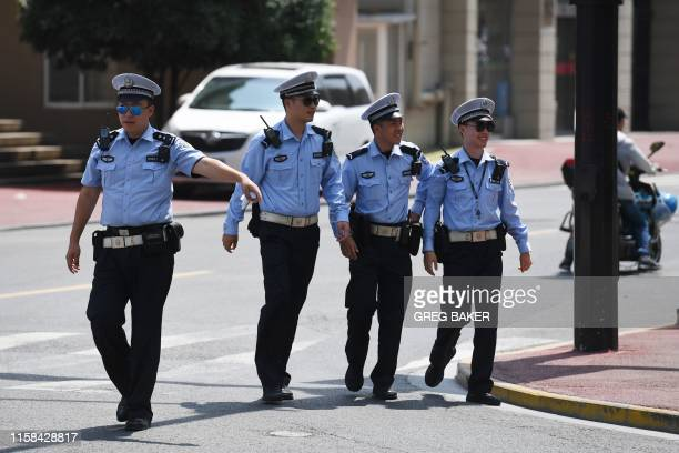 Traffic police stand outside a hotel after a convoy of cars believed to be carrying US trade negotiators arrived in Shanghai on July 30 2019 US and...