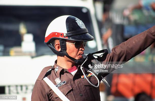 A traffic policeman blows his whistle in the busy streets of Bangkok The city is notorious for having some of the worst traffic jams in the world