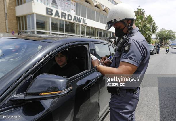Traffic policeman books an offender on highway north of the Lebanese capital Beiut on May 14 during a lockdown after new cases of coronavirus...