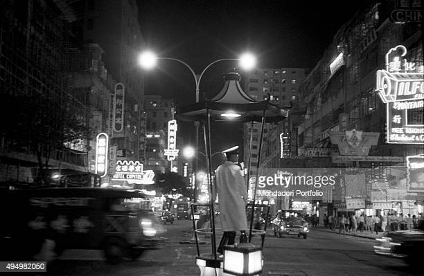 A traffic policeman directing the night traffic Hong Kong 1961