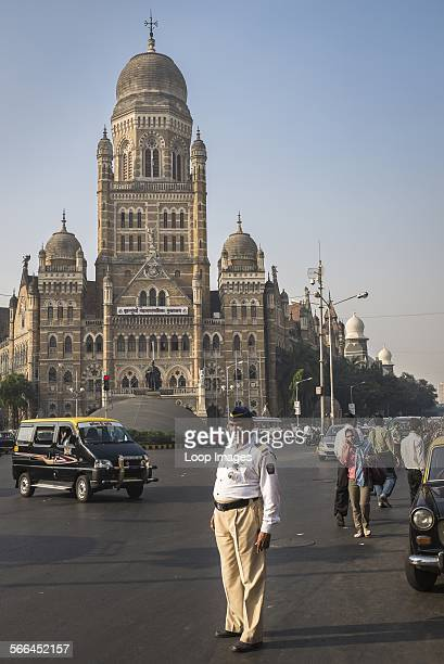 A traffic policeman observes traffic near the headquarters of the Municipal Corporation of Greater Mumbai