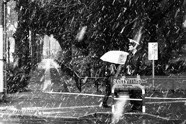 traffic policeman standing on road during snowfall - traffic police officer stock pictures, royalty-free photos & images