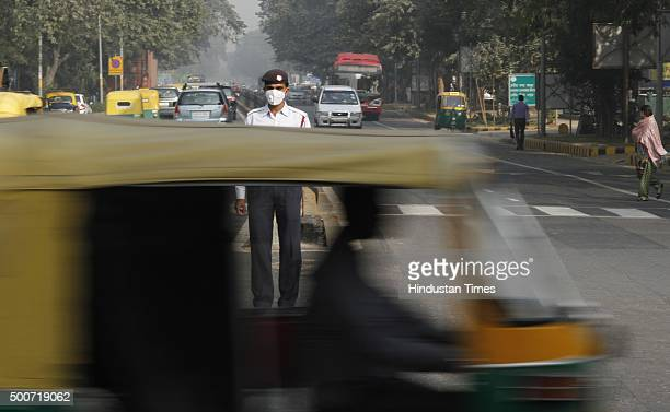 A traffic policeman wears antipollution mask while directing traffic on December 9 2015 at Janpath Road in New Delhi In an attempt to tackle the...