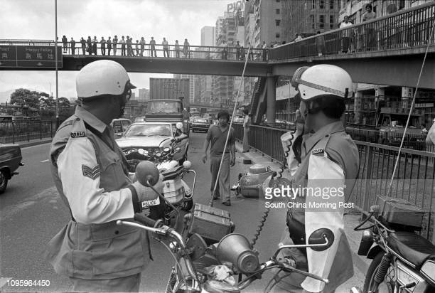 Traffic policemen inspecting the wreckage of a car on Waterfront Road after it collided with a motorcycle 04MAY77