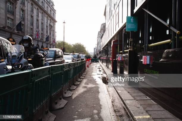 Traffic queues beside an unused area of temporarily expanded pavement, designed to aid social distancing, on Piccadilly in London, England, on...