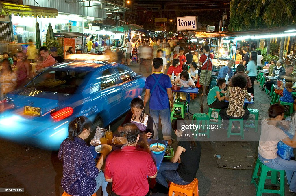 Traffic rolls by as a family tucks into dinner at a street food area in Banglumpoo district, Bangkok, Thailand..