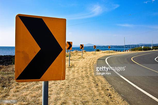 traffic sign at roadside - curved arrows stock-fotos und bilder