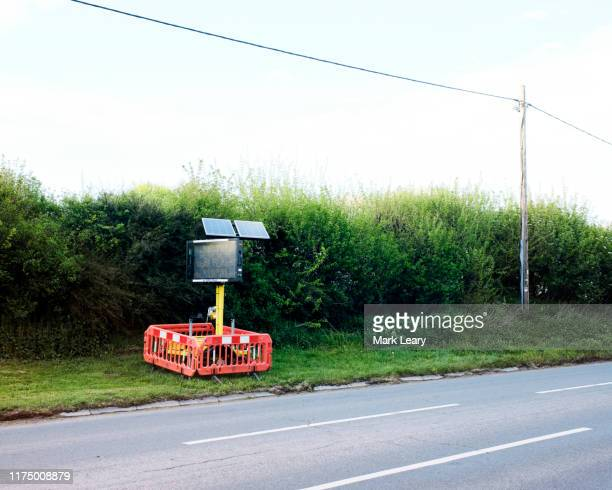 a traffic sign by the side of an empty road - newbury england stock pictures, royalty-free photos & images