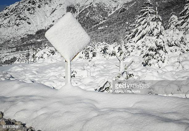 traffic sign covered with snow - radicella stock pictures, royalty-free photos & images