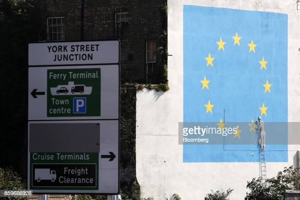 A traffic sign for the Port of Dover ferry terminal stands near a mural by street artist Banksy depicting a European Union flag being chiselled by a...
