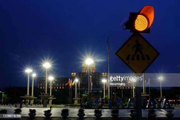 A traffic signal illuminates the street near the Perdana Putra the office complex of the Prime Minister of Malaysia in Putrajaya Malaysia on...