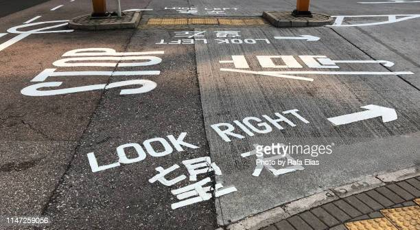 traffic signs on the ground, english and chinese languages - translation stock pictures, royalty-free photos & images