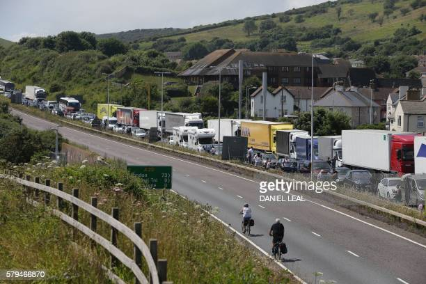 Traffic stands stationary in a traffic jam with travellers resting outside their vehicles on the main road leading into the port of Dover on the...