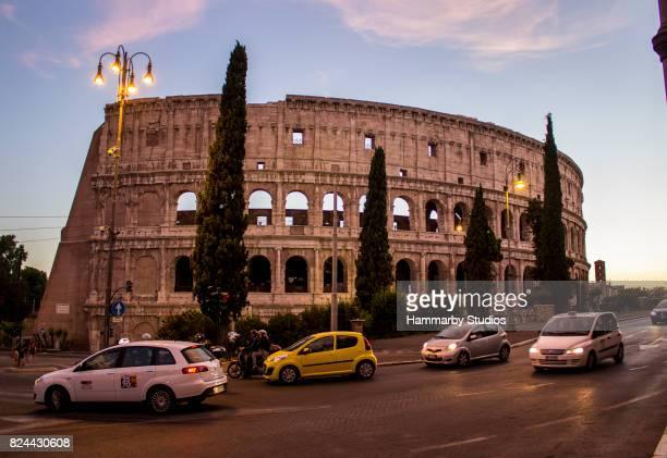 verkehrsstrom vor coliseum während des sonnenuntergangs in rom, italien - kleinere sehenswürdigkeit stock-fotos und bilder