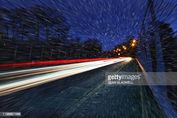 traffic tail lights at night in snow - horsedrawn stock pictures, royalty-free photos & images