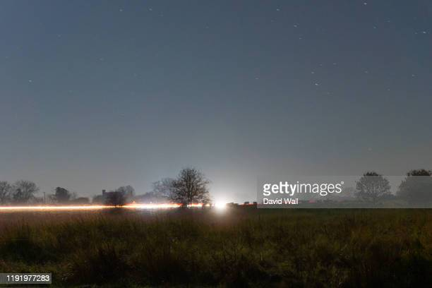 traffic trails going across common land with cows silhouetted in the distance. on a winters night in the countryside. - field stock pictures, royalty-free photos & images