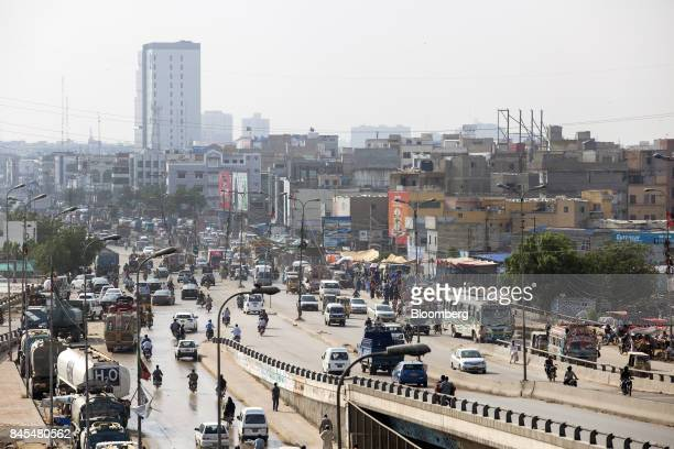 Traffic travels along a highway as a newly constructed apartment building stands in the background in Karachi Pakistan on Tuesday Aug 22 2017 The...
