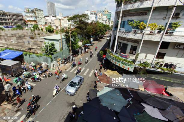 Traffic travels along a road past a market covered by parasols in Ho Chi Minh City Vietnam on Wednesday June 20 2018 For decades Vietnamese have...