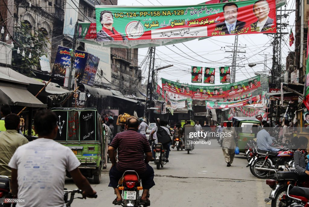 Traffic travels along a road past campaign banners for Pakistan TehreekeInsaf also known as Movement for Justice in Lahore Pakistan on Thursday July..