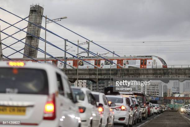 Traffic travels on the Western Express Highway as a train travels across the cablestayed Metro Bridge on Line 1 operated by the Mumbai Metro One Pvt...