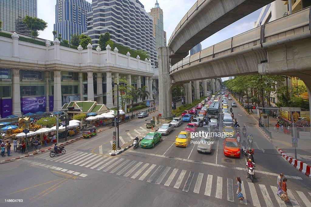 Traffic waiting at Ratchadamri Road intersection under the Skytrain rail tracks. : ストックフォト