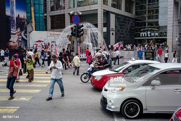 Traffic waits as pedestrians cross a street in Kuala Lumpur Malaysia on Friday Aug 5 2016 Malaysia's secondquarter gross domestic product figures are...