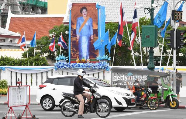 Traffic waits at lights during a public holiday with a portrait of Queen Sirikit behind on August 13, 2018 in Bangkok, Thailand. The holiday marks...