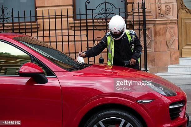 A traffic warden gives a parking ticket to a United Arab Emiratesregistered Porsche Cayenne Turbo S on July 23 2015 in London England London has...