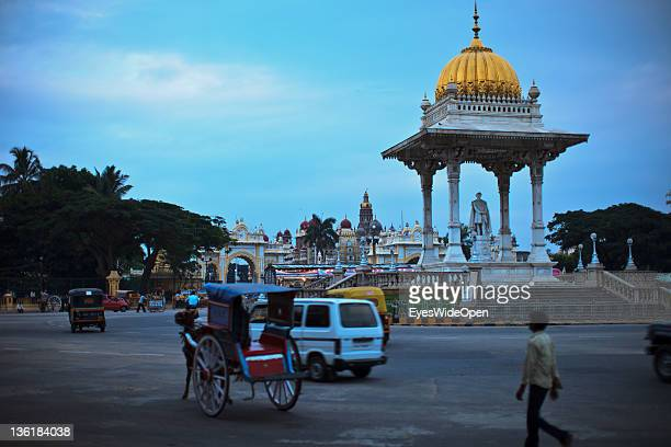 Traffic with buses a carriage horses motorbikes and cars at New Statue Circle or Chamaraja Circle roundabout at the Nothgate of Mysore Maharaja...