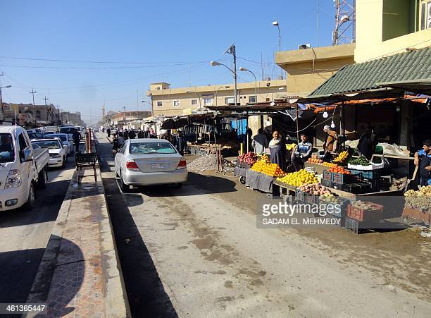 Traffice passes an open air market in the center of the city of Fallujah, west of the capital Baghdad on January 8 following days of fighting between...