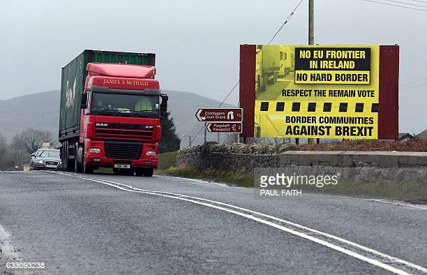 Trafic crosses the border into Northern Ireland from the Irish Republic next to a poster protesting against a hard brexit near Dundalk on January 30...
