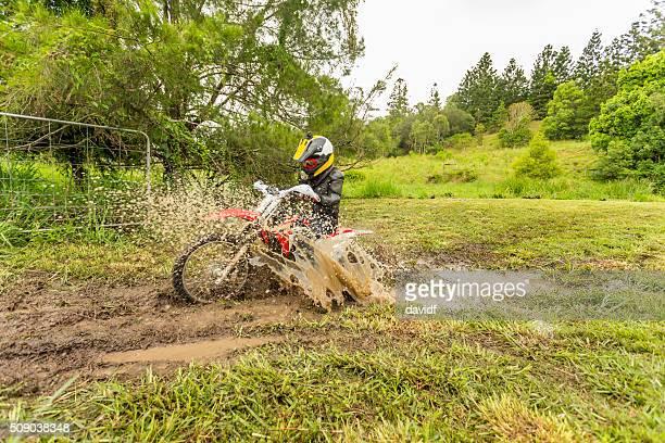 Trail Bike Splashing Through a Mud Puddle on a Farm
