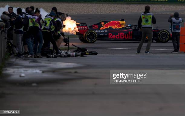 TOPSHOT A trail of smoke and flames is seen from the car of Red Bull's Australian driver Daniel Ricciardo during a practice session for the Formula...