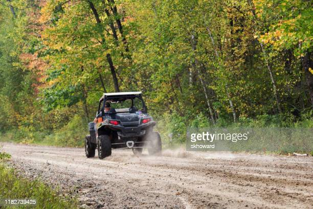 trail riding on 4x4 side-by-side off-road vehicle - side by side stock pictures, royalty-free photos & images