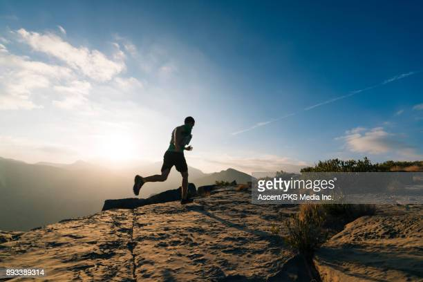 Trail runner ascending rocky trail above canyon at sunrise