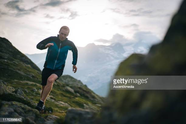 trail runner bounds along mountain meadow in the morning - forward athlete stock pictures, royalty-free photos & images