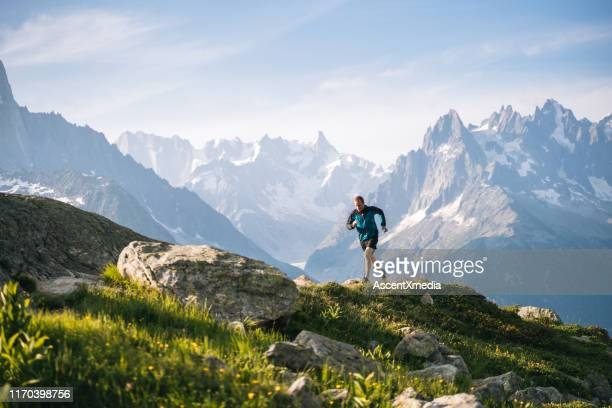 trail runner bounds along mountain meadow in the morning - cross country running stock pictures, royalty-free photos & images