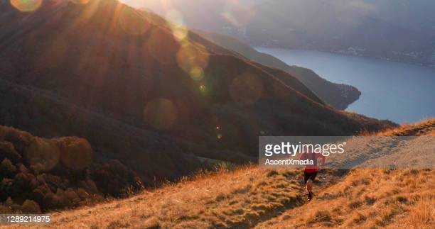 trail runner crosses mountain ridge in the morning - forward athlete stock pictures, royalty-free photos & images