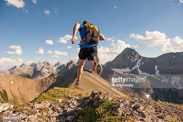 Trail runner in mid air stride, on mountain ridge
