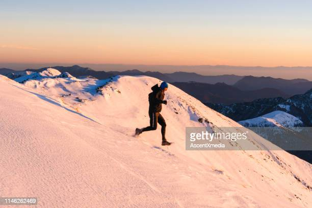 trail runner makes his way down snowy hill - forward athlete stock pictures, royalty-free photos & images