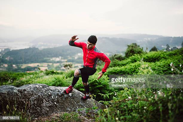 Trail runner man training in nature, on a rock