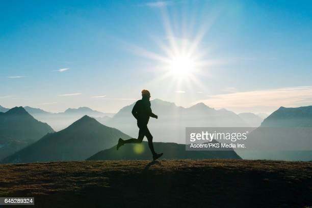 Trail runner strides across mountain summit, sunrise