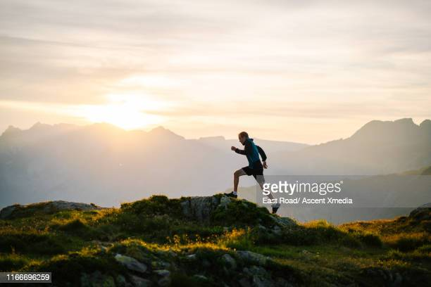 trail runner traverses mountain ridge crest - cross country running stock pictures, royalty-free photos & images