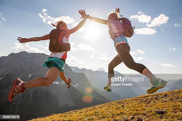 trail runners exchange mid-air high fives, summit - 30代の女性だけ ストックフォトと画像