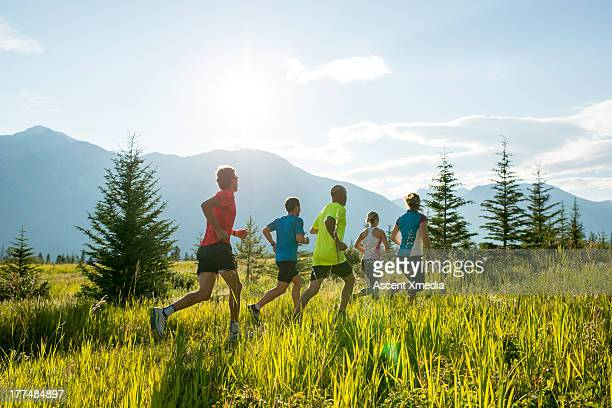 trail runners follow path through mtn meadow - running shorts stock pictures, royalty-free photos & images