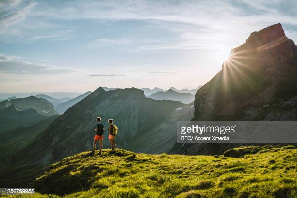 trail runners look off from summit of high alpine ridge - look back at early colour photography imagens e fotografias de stock