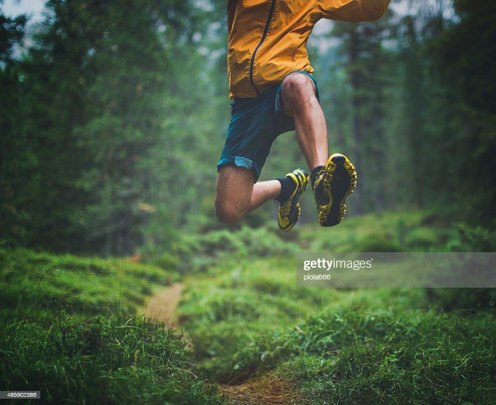 Trail running big jump : Stock Photo