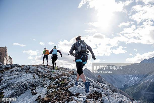 trail running friends ascend mountain ridge - sportkleding stock pictures, royalty-free photos & images