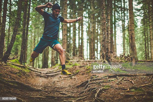 trail running in the forest: jumping roots - cross country running stock pictures, royalty-free photos & images